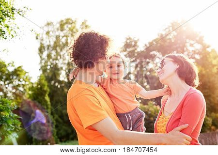 Family with child walks and plays in city park. A young father, mother and a small son dressed in orange t-shirt. The child funny dresses up sunglasses and plays with them. Child in the hands of his father