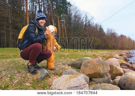 Mom and daughter throw stones into the water on vacation. Happy people on the lake in the country spend time with their family. A woman and a child in the park play against the backdrop of a landscape of forest, stones and a lake.