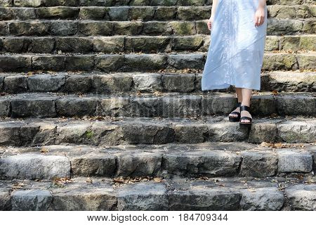 Young woman standing on the steps of a stone