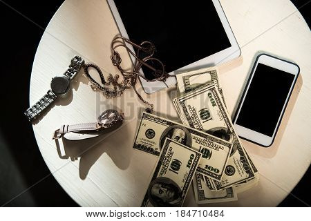 Top view of dollar banknotes wristwatches jewelry and digital devices on wooden table