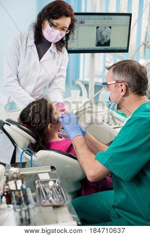 Young Girl With On The First Dental Visit. Senior Pediatric Dentist With Nurse Treating Patient Teet