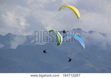 Paragliders flying their wings in the French Alps