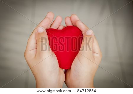 Child holds a big red heart in his hands. Sincerity, sincere love or philanthropy stock image.