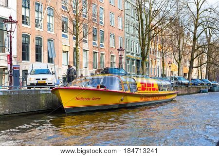 Amsterdam, Netherlands - April 1, 2016: Traditional old buildings, canal and DHL boat in Amsterdam, the Netherlands