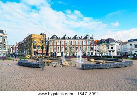 Hague, Netherlands - April 6, 2016: Street view with traditional dutch houses, fountain and spring tree blossom in Hague, Holland