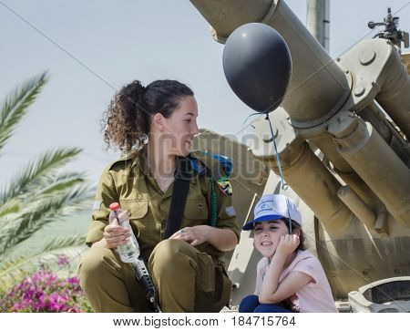 Unidentified Israeli Girl-soldier  Sit On Tank Armour With Child At Latrun Armored Corps Museum
