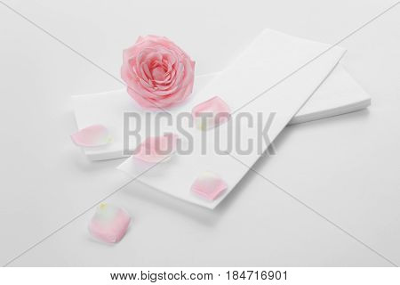 Wax strips for epilation and flower on white background