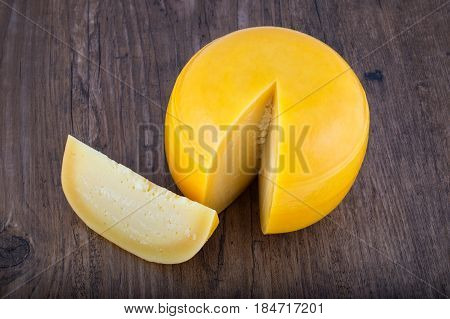 Cheese head with a slice cut off on wooden table