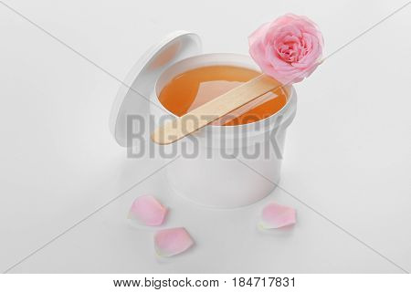 Plastic bucket with sugaring paste, stick and flower on white background