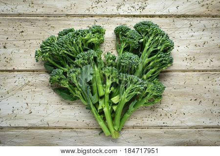 high-angle shot of some stems of broccolini forming a heart on a wooden rustic table