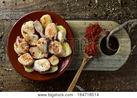 high-angle shot of an earthenware plate with pulpo a la gallega, a recipe of octopus typical in Spain served on potatoes and seasoned with paprika, on a rustic wooden table