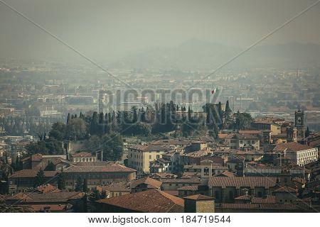 View at Old Town Citta Alta of Bergamo from San Vigilio Hill. Bergamo, Italy. Flag