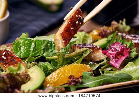 Japaneese cuisine. Eating green salad with smoked eel, slices of avocado and orange. Closeup of bamboo sticks holding fish slice.