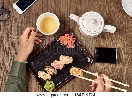 Flatlay. Closeup of woman hands with bamboo chopsticks eating sushi with green tea.