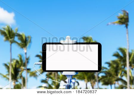 Selfie monopod stick with mobile phone tropical background empty space for text white screen