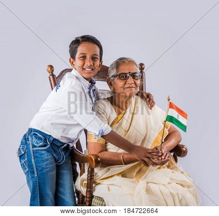 indian family holding indian national flag over white background, indian kids and grandmother with flag