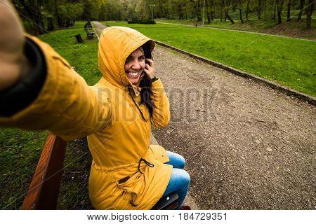 Cute happy young woman in hood taking selfie in windy day