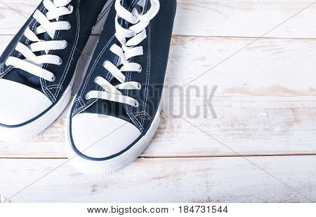 Youth classic gumshoes with white the laces on wooden background