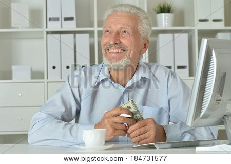 Old businessman with a laptop working in the office