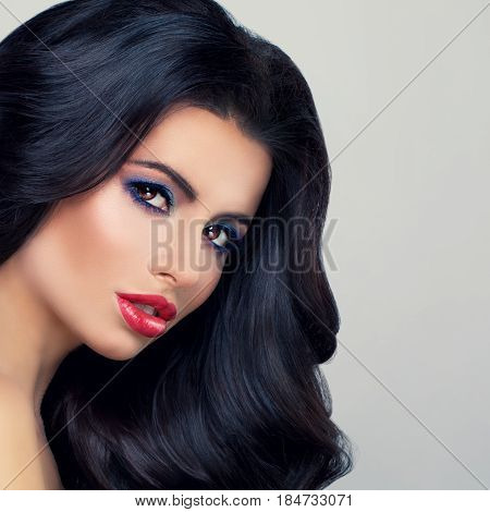 Glamorous Brunette Woman Fashion Model with Long Curly Hair and Red Lips Makeup