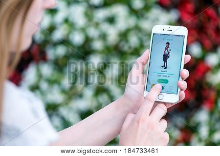Varna Bulgaria - Jul 19 2016: Nintendo Pokemon Go augmented reality mobile application profile page with game character on Apple iPhone 6S in female hands. Blurred flowers view on the background.