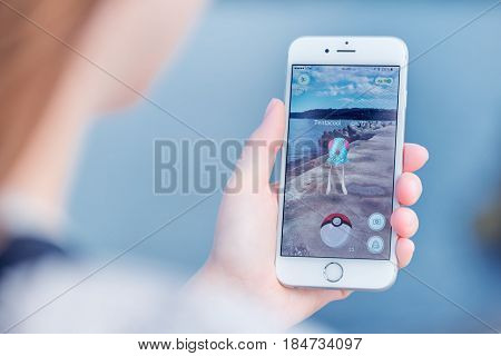 Varna Bulgaria - Jul 19 2016: Nintendo Pokemon Go augmented reality mobile application game with Tentacool pokemon catching on Apple iPhone 6S in female hand. Blurred view on the background.