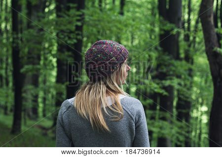 horizontal rear view portrait of Caucasian young woman with long blonde hair and colorful wool hat standing in a green forest