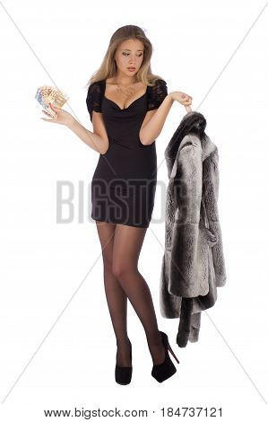 Attractive young woman with a fur coats and money on white background