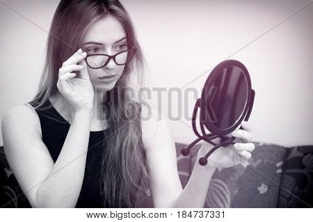Woman With Glasses Looking In The Mirror
