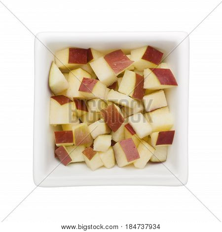 Diced red apple in a square bowl isolated on white background