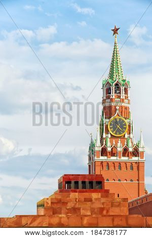 Red square Moscow Russia. Spasskaya tower of Kremlin with star and clock and Lenin's Mausoleum. Vertical composition copy space on the cloudy sky. Bright and sunny day view