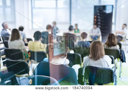 Round table discussion at business and entrepreneurship symposium. Audience in conference hall. Lens focus on unrecognized participant in rear of audience. Shot trough glass.