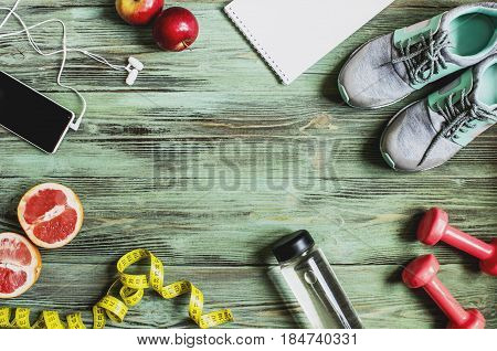 set of sports props fruit water spread out on a wooden surface of a turquoise top view