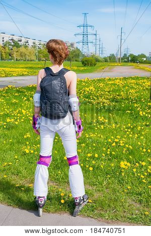 Active young woman in sportswear on roller skates. Stand with back and look into the distance. Against bright green field with flowers and distant cityscape. Skating leisure and sport lifestyle theme