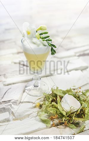 Bright yellow alcohol cocktail with egg garnish with Linden flowers and hen figure on white background