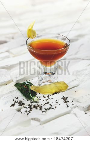 Bright orange alcohol cocktail garnished with ginger and lemon slice on white background