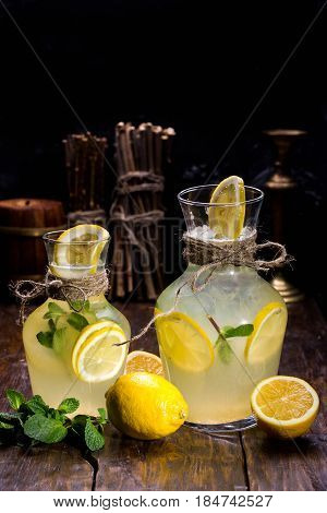 Lemonade with segments of a lemon and mint. Is served in a big jug with ice. Is served in a small jug with ice.