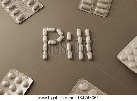 White Pills. Forming The Word - Pill. Near Are Tablets Over Grey Background
