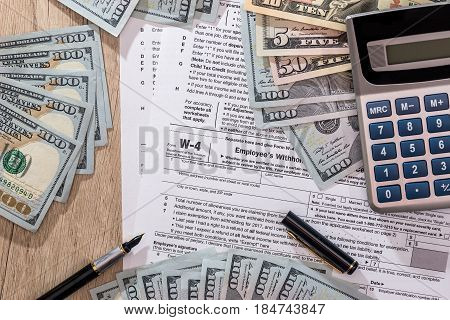 W4 Tax Form With Money, Pen And Calculator On Desk.