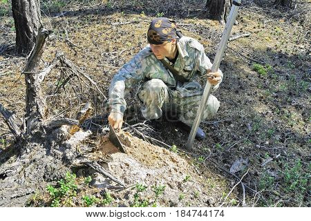 A young archaeologist in search of finds in the field expedition in Siberia