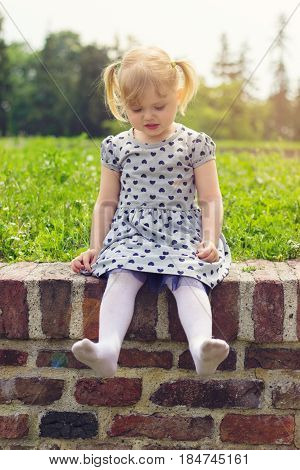 Little girl sitting on the wall happy to be barefoot she took her shoes off