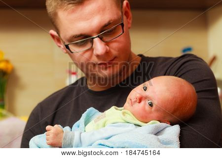 Father Holding Little Newborn Baby In Blanket