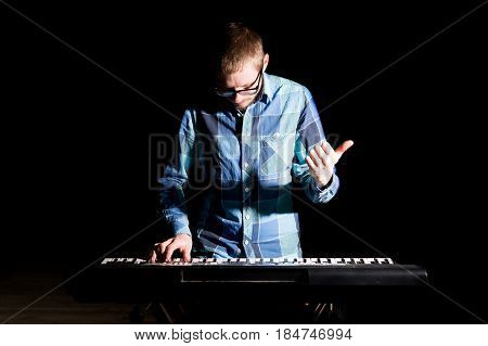 Young Musician In Plaid Shirt Playing Electric Piano In A Nightclub Over Dark Background