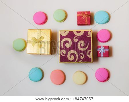 Macaroons and gift boxes on beige background. Top view