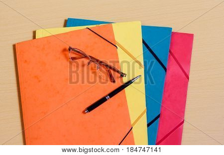 Office folders,  glasses and pen on desk