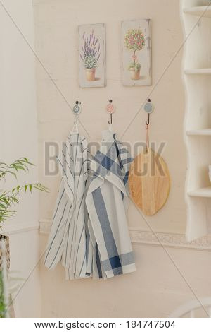 On the wall with paintings hang kitchen towels and a cutting board
