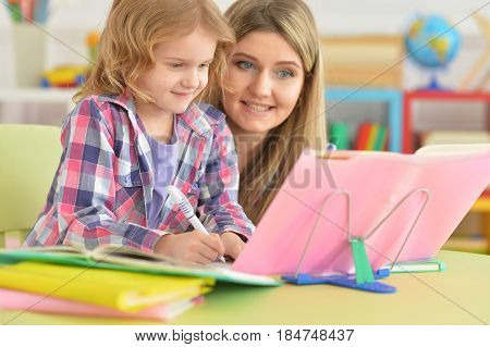 Mother and daughter doing their homework in the room