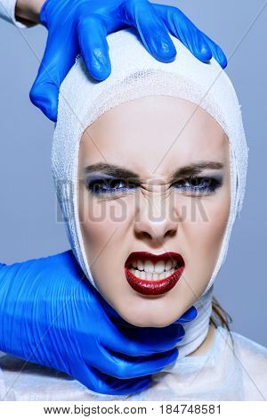 Beauty, fashion and medicine, plastic surgery. Portrait of a shouting young woman in bandages and hospital gown. Studio shot.