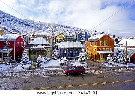 A row of colorful houses covered in snow on a street, with snow covered mountains behind