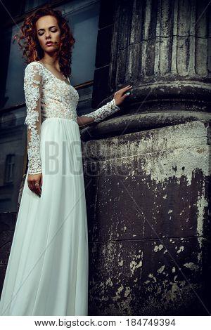 Beautiful fashion model in luxurious white dress on a city street. Charming bride woman walking down the street. Beauty, fashion.